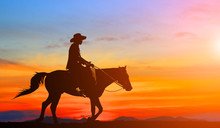 Silhouette Cowboy And Horse On Blurry Colorful Sunset Sky.