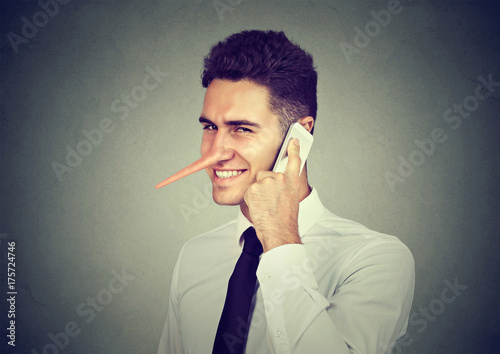 Fotografering  Sly young man with long nose talking on mobile phone isolated on gray wall background