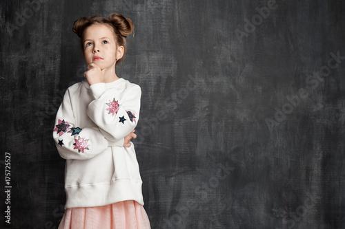 Plakat Śliczna mała dziewczynka stoi zadumie na chalkboard tle z bezpłatnym siedzeniem po prawej
