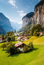 Great View Of Alpine Village Glowing By Sunlight. Location Swiss Alps, Lauterbrunnen Valley, Staubbach Waterfall, Europe.