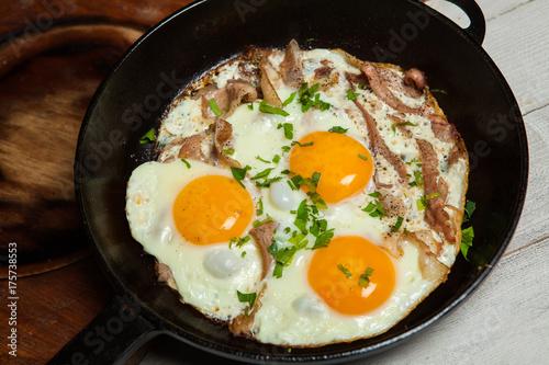Plakat Smażone jajka na patelni z bekonem. Jajka sadzone z bekonem w panierce przyprawione ziołami i pieprzem.