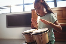 Girl Playing Bongo Drums In Cl...