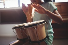 Mid Section Of Girl Playing Bongo Drums