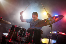 Male Musician With Drumsticks Playing Drums