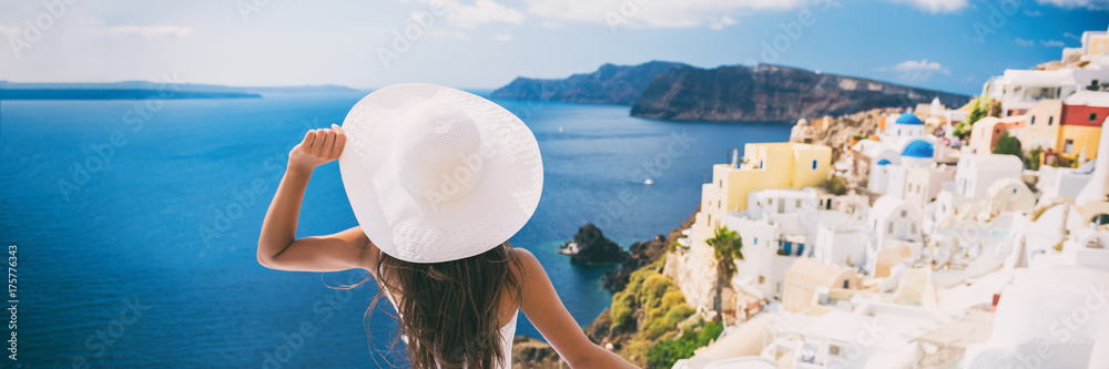 Fototapeta Luxury travel vacation woman in Santorini banner. Europe cruise ship destination holiday tourist looking at sea view with sun hat in Oia, Greece.