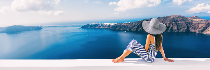 Travel luxury cruise vacation holiday woman panoramic banner. Sun hat maxi dress woman relaxing at sea view in Santorini, Oia, Greece. Europe destination.