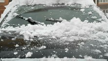 Close Up View Of The Car In Front - Windshield Wipers Work And Wind The Snow From The Windshield During The Snowfall In Winter