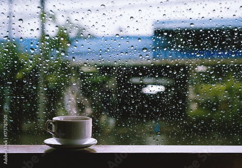 Foto Cup of Hot Drinks on wooden table in rainy day