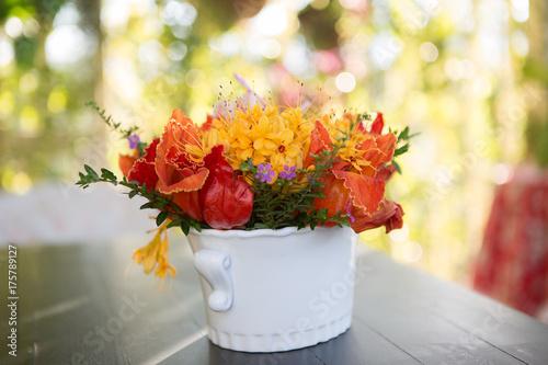pomaranczowe-kwiaty-w-bialym-kubeczku-na-tle-ogrodu