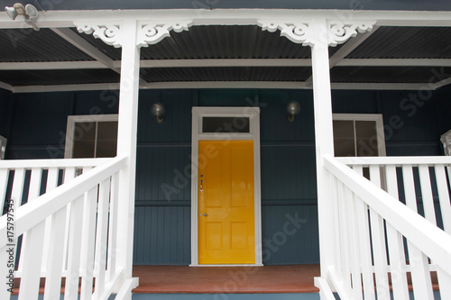 Details of a freshly painted Queensland colonial home with a welcoming sunshine yellow front door.