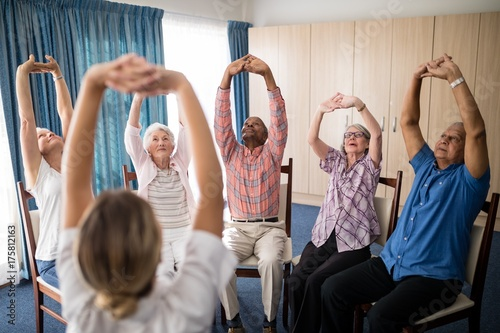 Fotografía  Female doctor stretching with seniors sitting on chairs