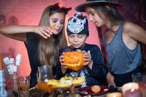 Portrait Of Three Happy Children Wearing Halloween Costumes Two