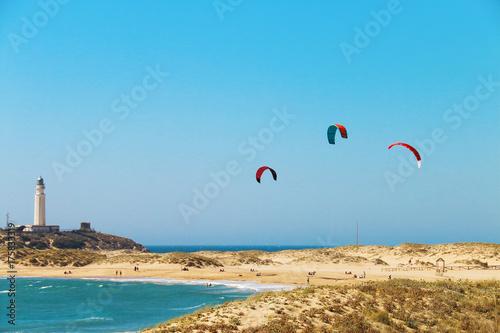 People doing kitesurfing on the beach of Los Canos de Meca, next to the lighthouse of Trafalgar, on the coasts of Cadiz, Spain