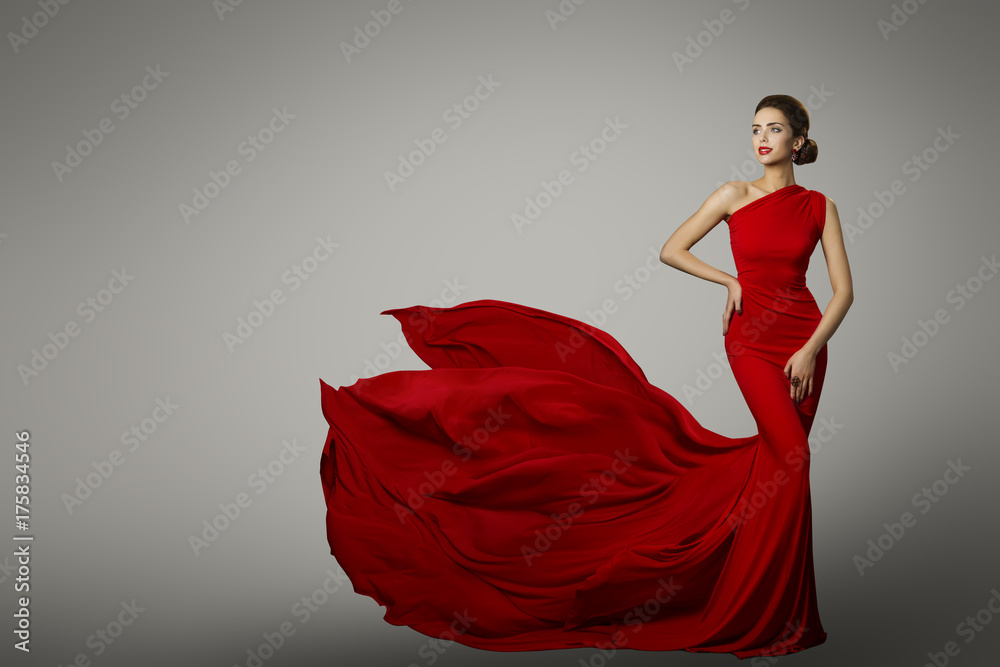 Fototapeta Fashion Model in Red Beauty Dress, Sexy Woman posing evening Gown, Flying Silk Tail over gray background