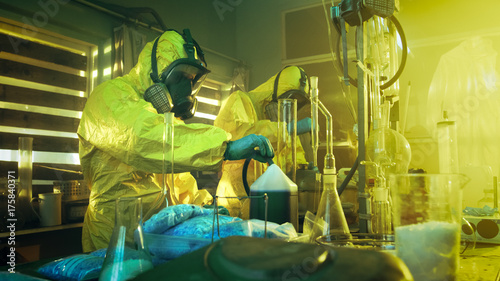 Fotografie, Obraz  In the Underground Laboratory Two Clandestine Chemists Wearing Protective Coveralls and Masks Cook Drugs