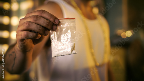 Fotografija  Brutal Drug Dealer Wearing Sleeveless Shirt and Gold Chain Holds and Offers Sample Bag Full of Drugs