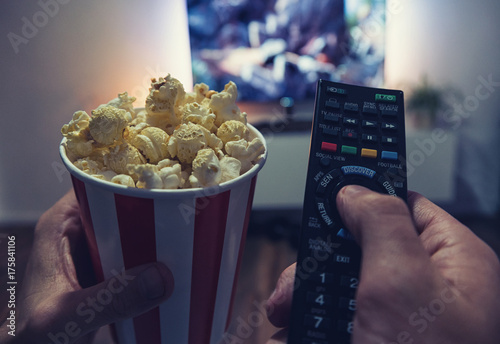 Fotografía  young man Watching a Movie in his living room with popcorn and remote control, P