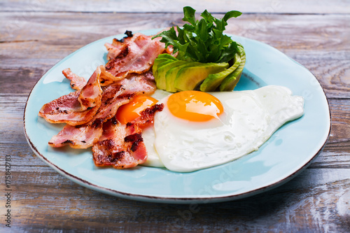 Continental breakfast with fried eggs, bacon and avocado. Ketogenic diet concept. Space for text