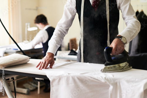 Stampa su Tela Closeup of stylish tailor ironing fabric with steaming antique iron on board in