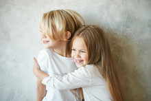 Two Happy Kids Standing At Blank Grey Wall And Embracing. Adorable Pretty Little Girl With Long Hair Hugging Tight Cute Blonde Boy, Showing Her Love And Care. Brother And Sister Having Fun At Home