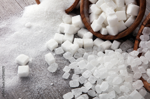 Fotografia Bowl with white sand, crystal and lump sugar on wooden background