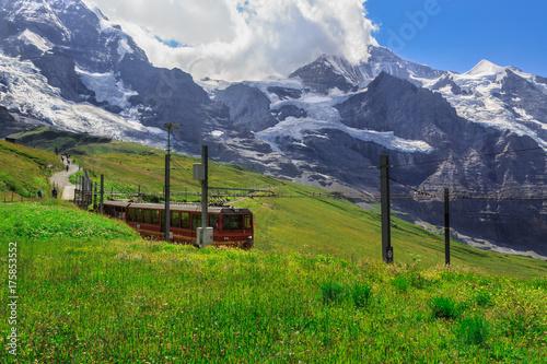 Zdjęcie XXL Słynny czerwony pociąg schodzący z Jungfraujoch Top of Europe do Kleine Scheidegg. Zdjęcie letnie - Kleine Scheidegg, Oberland Berneński, Szwajcaria