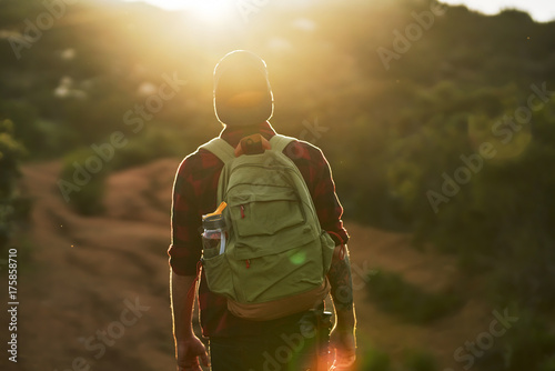 Fototapeta male millennial hiker trekking up trail in southern california during sunset obraz