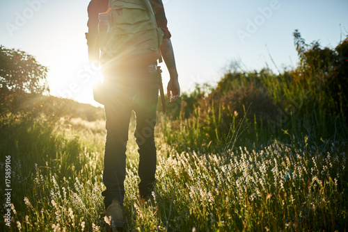 Fototapeta male millennial hiker walking through grass in southern california during sunset obraz