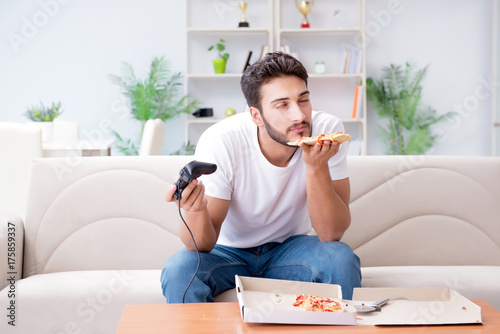 Man eating pizza having a takeaway at home relaxing resting Tablou Canvas