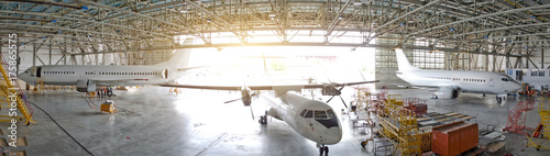 Fototapeta Three passenger aircraft in a hangar with an open gate for service, view of the panorama. obraz