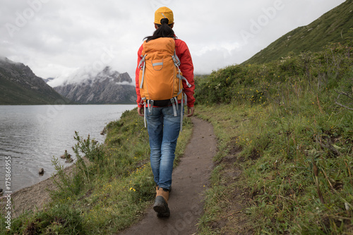 Fotografiet young backpacking woman hiking in the nature