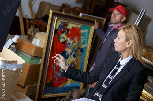 Photo female auctioneer showing her assistant which paintings to take