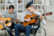 Young Men Playing Guitar, One In A Wheelchair