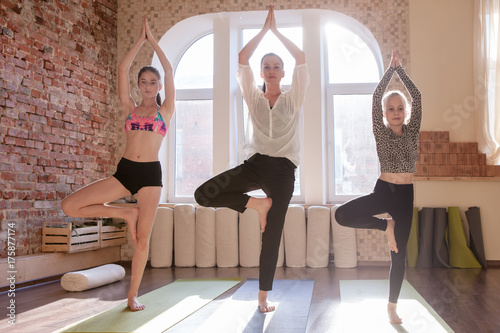 Tuinposter Gymnastiek Girls gymnastics. Teenage yoga class. Children workout together with female instructor, gym bright background. Healthy family lifestyle, stretching exercise