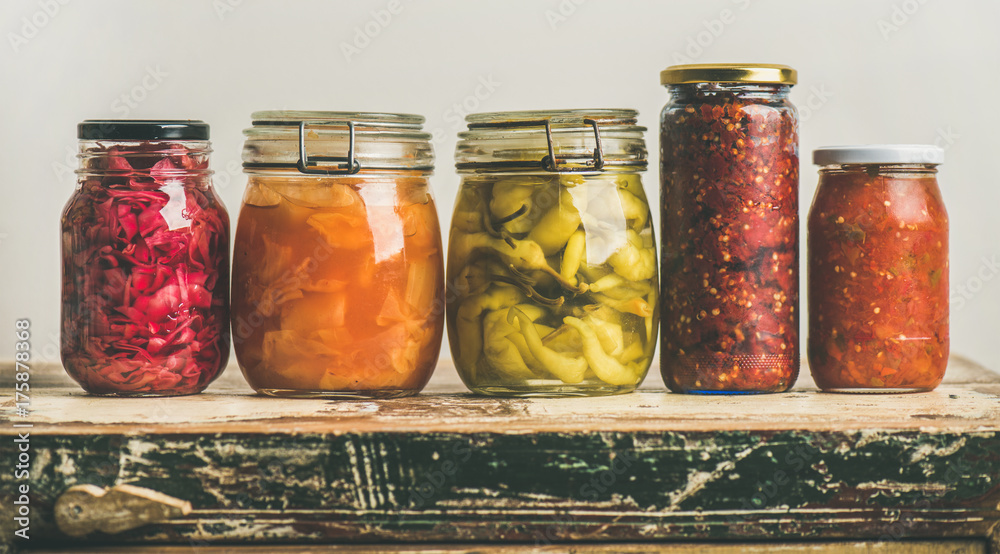 Fototapety, obrazy: Autumn seasonal pickled or fermented vegetables in jars placed in row over vintage kitchen drawer, white wall background, copy space. Fall home food preserving or canning