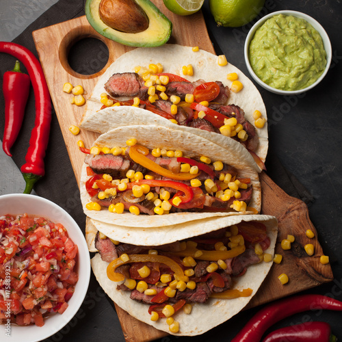 Keuken foto achterwand Assortiment Three Mexican tacos with marbled beef, black Angus and vegetables on wooden Board on a dark stone background. Mexican dish with sauces guacamole and salsa in bowls. Top view