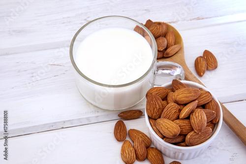 Zdjęcie XXL Zamyka w górę zdrowego migdału mleka w pić szklanym z ziarnem w białej filiżance i drewnianej łyżce na białym drewnianym stołu talerzu z kopii przestrzenią