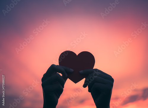 Closeup hand holding red heart during sunset background. Happy, Love, Valentine's day idea, sign, symbol, concept.