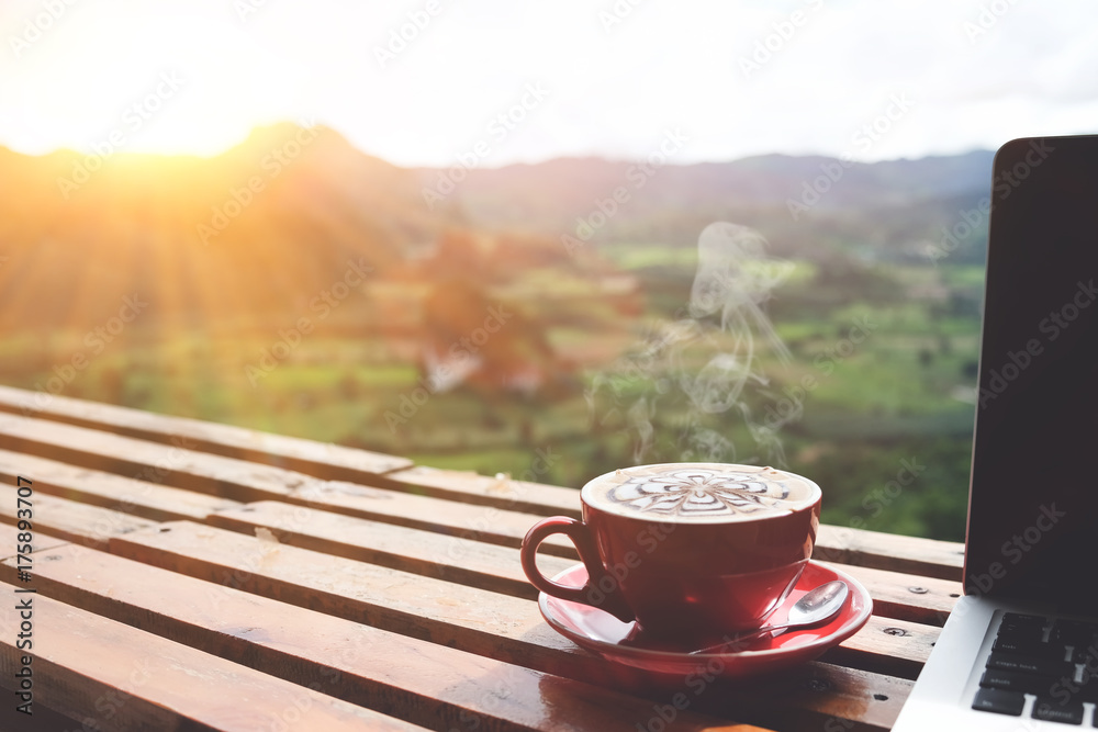 Fototapeta Coffee morning and laptop on wooden table with beautiful mountain background. Worklife balance concept