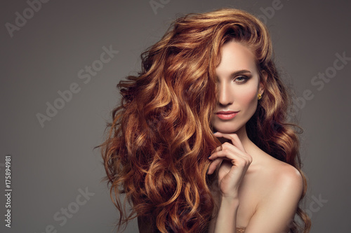 Foto Portrait of woman with long curly beautiful ginger hair.