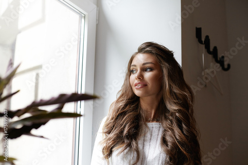 Fototapeta  Beautiful well-pleased young Caucasian woman enjoying ideal day, standing at large window and looking outside with dreamy thoughtful smile