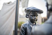 Black Metal Or Bronze Garden Statue Of A Victorian Boy Wearing A Flat Cap