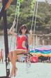 Beautiful young female sitting on the swing on sea shore. Bali island, Indonesia. Pandawa beach.