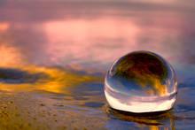 Summer Sunset Displayed Through A Transparnt Glass Ball On The Beach Sand