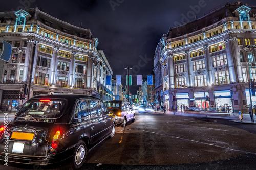 Obraz na dibondzie (fotoboard) Londyn, Wielka Brytania. Około sierpnia 2017 r. Czarna taksówka w Londynie. Ruch pieszy i ruchu w Oxford Circus w nocy