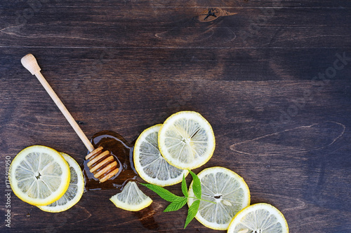 Photo  On a wooden texture background a lemon and honey