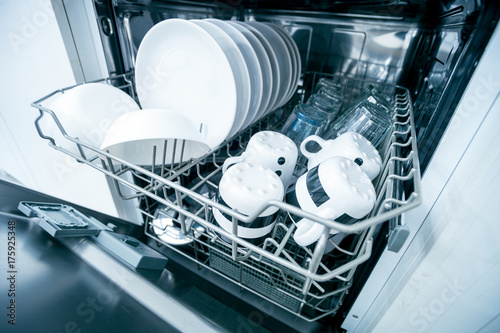 Open dishwasher with clean dishes close up