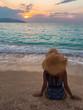 Chica sentada en la playa mirando el atardecer