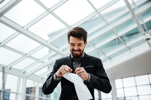 Valokuva  Businessman tearing sheet of paper with a smile on my face