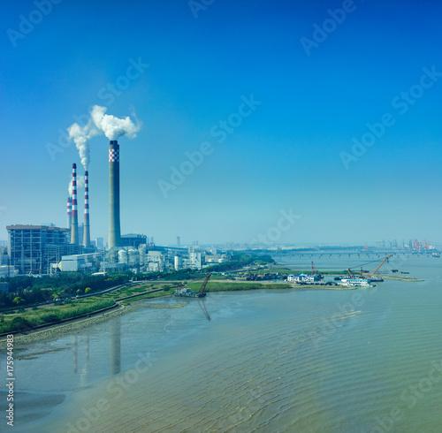 Photo  Smoking smokestack of chemical plant near gulf with blue sky